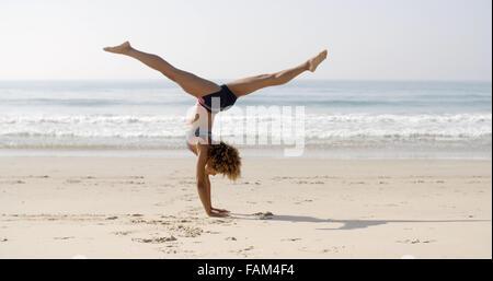 Young Woman Doing Cartwheel On The Beach - Stock Photo