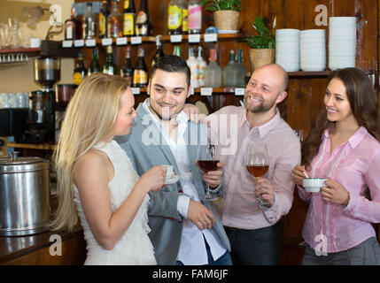 Group of smiling young adults hanging out in bar with drinks. Focus on guy - Stock Photo