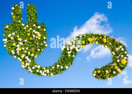 Grass and flowers covered electrical plug and cord - Stock Photo
