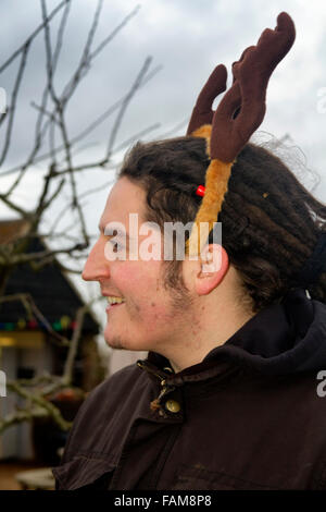Man with dreadlocks wearing a decorative Christmas reindeer antlers head band - Stock Photo