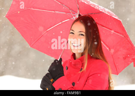 Beauty woman in red with an umbrella in a snowy winter - Stock Photo