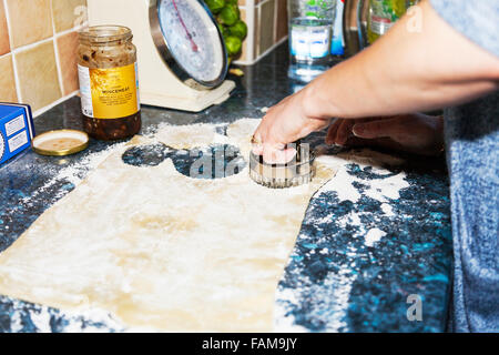 Cutting Pastry cutter shape rolled out sheet ready for cutting flower kitchen worktop cooking baking woman working - Stock Photo