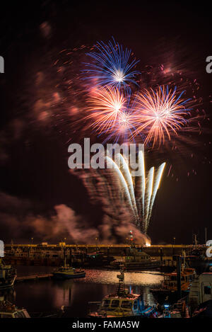 New Year Eve firework display at Ramsgate Royal Harbour with the commercial fleet in the foreground. - Stock Photo