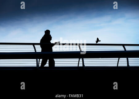 The silhouette of two people and a bird on the Millenium Bridge in London. - Stock Photo