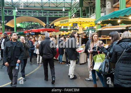 Shoppers and tourists in Borough Market in London. - Stock Photo