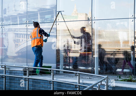 Window cleaner at work - a worker cleaning the windows of Blackfriars Station on the South Bank in London. - Stock Photo