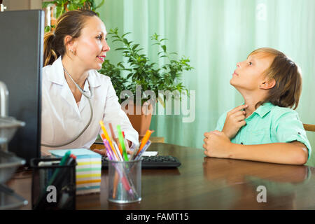 Teenager boy complaining of pain in throat to female doctor - Stock Photo