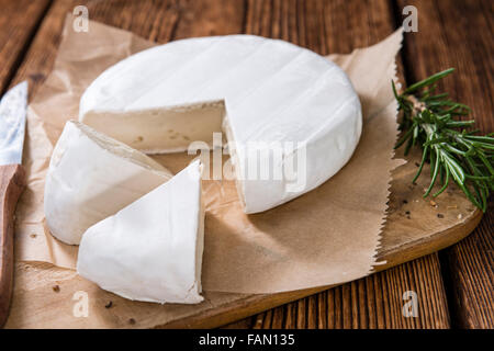 Pieces of creamy Camembert (close-up shot) on vintage wooden background - Stock Photo