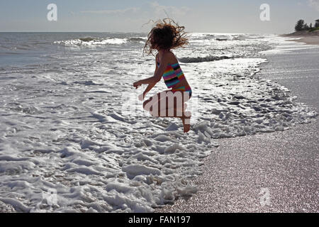 Girl jumping over waves at the beach. - Stock Photo