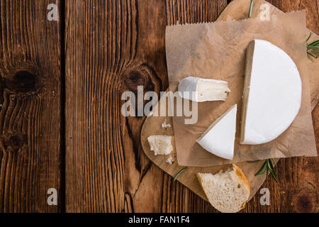 Pieces of Camembert (detailed close-up shot) on wooden background - Stock Photo