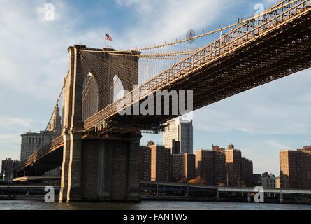 Brooklyn Bridge entering Manhattan with an American flag flying - Stock Photo
