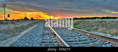 Panoramic view of train tracks leading into the distance - Stock Photo
