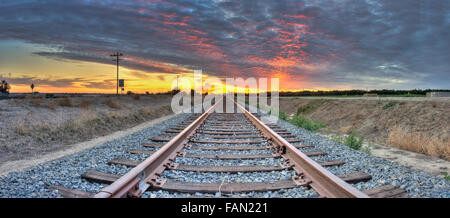 Panoramic view of train tracks leading into the sunset - Stock Photo