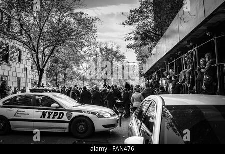 A crowd of spectators watch the 2015 Macy's Thanksgiving Day Parade and a NYPD cop car in black and white - Stock Photo