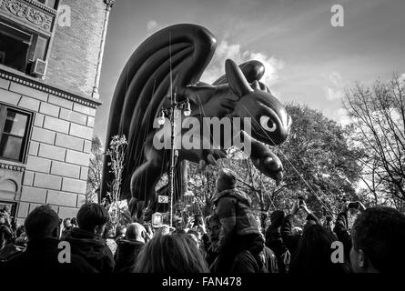 A crowd of spectators watch the Toothless balloon at the 2015 Macy's Thanksgiving Day Parade in black and white - Stock Photo