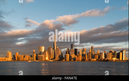 The skyline of downtown Manhattan appears golden as the sunset opposite is reflected in the glass of the skyscrapers - Stock Photo