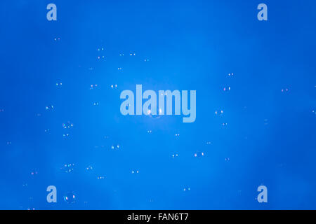 Soap bubbles floating in the air with blue sky in the background - Stock Photo