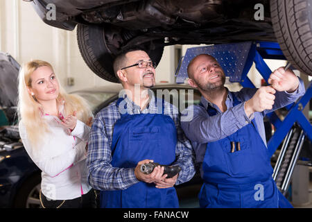 Mechanics and a woman in a repair shop are examining suspension under a lifted up car - Stock Photo