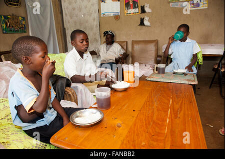 Family enjoying a meal of boiled rice around table  in their home, Kenya. - Stock Photo