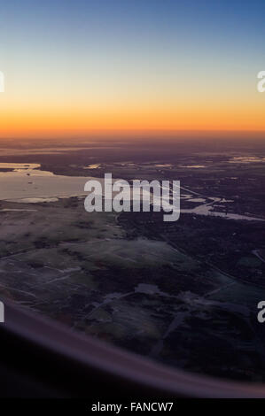 Amsterdam (North Holland, The Netherlands) at sunrise aerial view from jet airplane aircraft porthole - Stock Photo