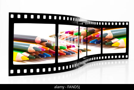 Film Strip with Coloured crayons on a white background - Stock Photo