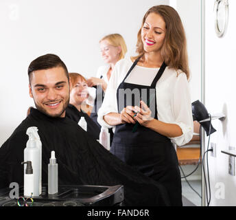 Cheerful young guy cuts hair and female barber at the hair salon - Stock Photo