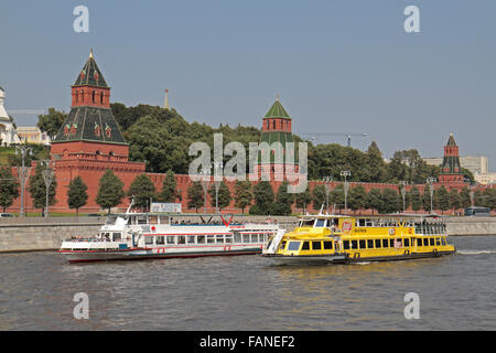 Tourist boats on the Moskva River passes the walls of the Kremlin in Moscow, Russia. - Stock Photo