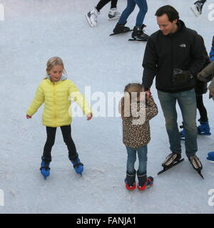 Man and two girls skating at the temporary skating rink on Museumplein (Museum Square), Amsterdam, The Netherlands - Stock Photo