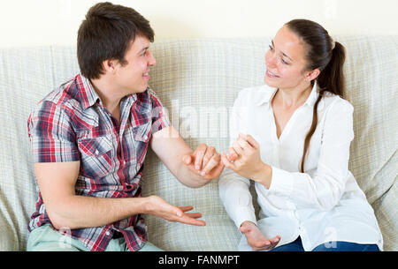 Loving young couple is reconciled sitting on couch and smiling - Stock Photo