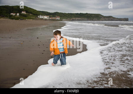 A young boy playing on the beach at Saltburn, Yorkshire. - Stock Photo