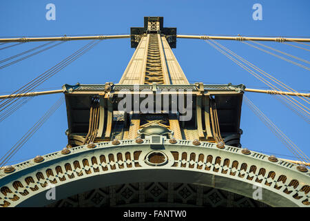 Beaux-Arts style architectural detail of the Manhattan Bridge Tower with arch and cables at sunset, Brooklyn, New - Stock Photo