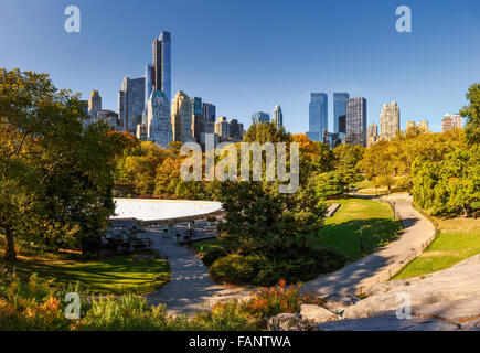 Fall in Central Park: Wollman Rink and Manhattan skyscrapers. Cityscape autumn view of Central Park South, New York - Stock Photo