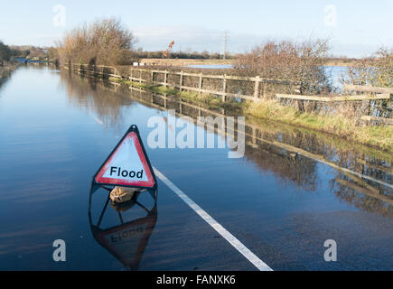 A closed flooded minor road with a triangular flood warning sign, north east England, UK - Stock Photo