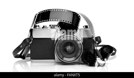 Old 35mm film photo camera on white background with 35mm film strip - Stock Photo