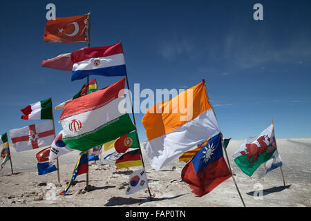 Flags of different countries fly from posts on the Salar de Uyuni (Salt Flats of Uyuni) in Bolivia - Stock Photo