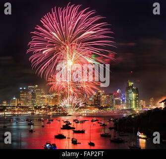 New year fireworks in Sydney from elevated lookout at Berrys bay over Sydney harbour with CBD skyscrapers under flash balls Stock Photo
