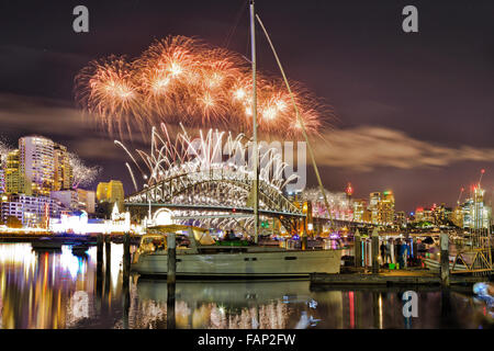 brightly lit city of Sydney during new year night and fireworks over Sydney Harbour Bridge reflecting in still waters - Stock Photo