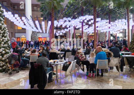 Visitors and shoppers sit under hanging lanterns in the atrium of Brookfield Place during the holiday season in - Stock Photo