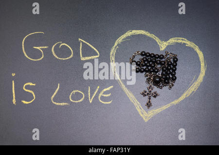 In the picture a rosary iron at the center of a heart drawn on the left side the word 'god is love' with a crayon - Stock Photo