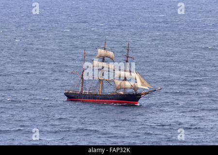 tall ship with sails at open sea on a sunny day aerial side-view during race with tourists on board of upper deck - Stock Photo