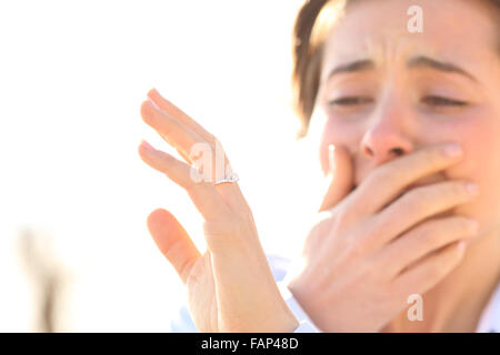 Woman crying while watching an engagement ring after proposal in a sunny day - Stock Photo