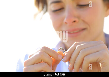 Sad girlfriend crying while is looking her engagement ring - Stock Photo