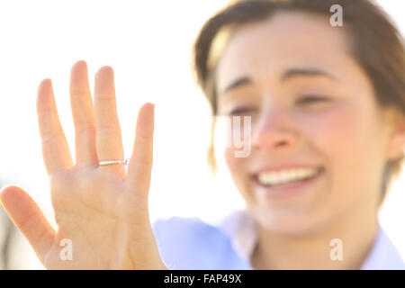 Happy woman looking an engagement ring after proposal in a sunny day - Stock Photo