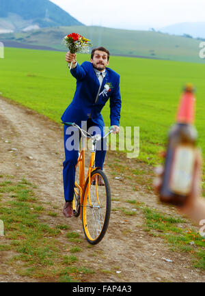 drunken groom on a bike holding a wedding bouquet is running after a bride with a beer bottle - Stock Photo