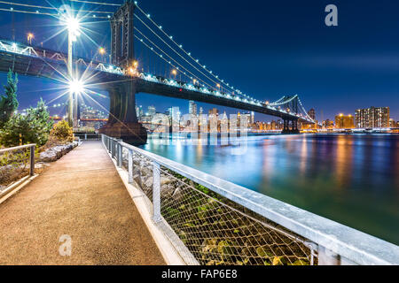 Manhattan Bridge by night, viewed from John Street Park with Brooklyn Bridge and Lower Manhattan skyline in the background. Stock Photo