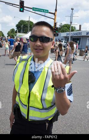 Asian volunteer policeman age 23 directing traffic. Grand Old Day Street Fair. St Paul Minnesota MN USA - Stock Photo
