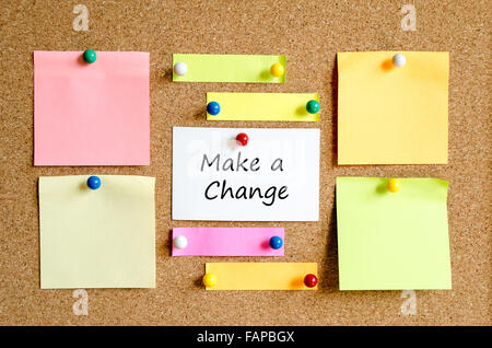 Colorful sticky notes on cork board background and text concept make a change - Stock Photo