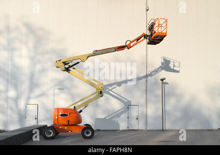 little mobile hydraulic crane making a shadow against the wall - Stock Photo