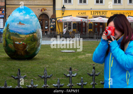 A Japanese take pictures with a Polaroid in the gardens located in front of the Café Lippert front of the Old Town - Stock Photo