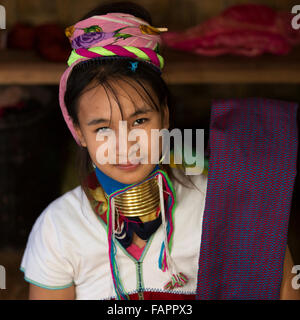 A woman from the Kayan tribe weaving in a workshop at Inle Lake in Myanmar (Burma). The woman wears brass coils on her neck.